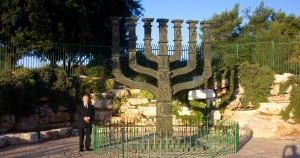 Yisrayl Hawkins stands beside a Menorah in Isreal