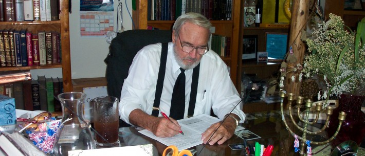 Yisrayl Hawkins working on one of his books at his desk